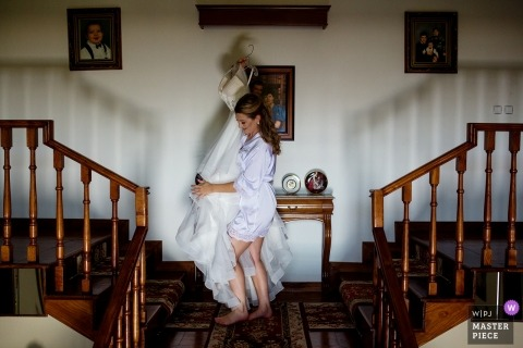 Guimarães, Portugal Wedding Photojournalist | the bride heads upstairs with her dress still on a hanger