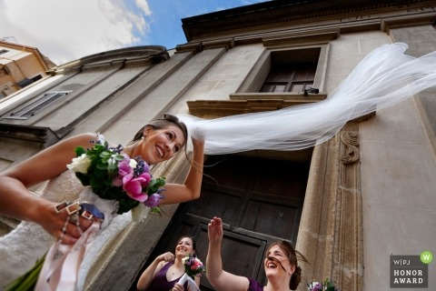 Bridesmaids and bride trying to stop the vale from flying away in this Reggio Calabria wedding photo