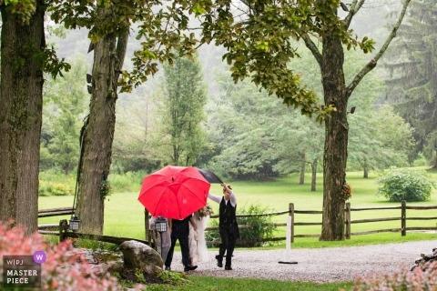 New Jersey Wedding Fotojournalist | Kleurenfoto van de bruid die aan de ceremonie onder een rode paraplu loopt