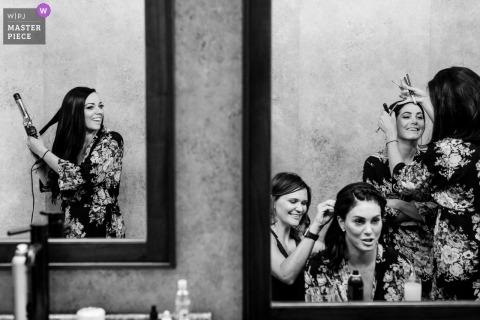 Hamilton, Montana Wedding Fotojournalist | de bruid en het bruidsmeisje werken aan hun haar in spiegels terwijl ze zich klaarmaken