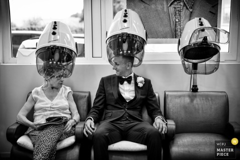 Ancona Wedding Photojournalist | the groom is at the hair salon under a hairdryer
