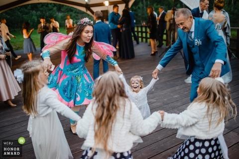 Bloemmeisjes in Rusland die bij de ontvangst met de bruid en de bruidegom dansen