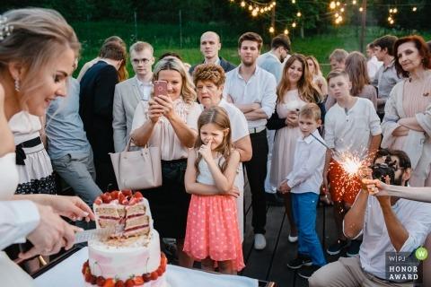 Rusland-gasten kijken toe terwijl de bruid de taart snijdt tijdens dit outdoor huwelijksfeest