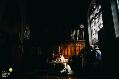 Ss Peter e Paul Kettering - noiva e noivo assinando o registro abaixo luz janela maravilhosa