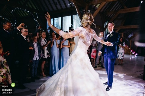 Bride and groom enjoying their first dance as guests watch at the Red House Barns