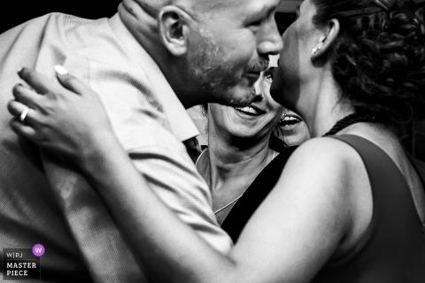 Photojournaliste de mariage à Budapest | Hongrie Membres de la famille s'embrassant à la réception - Photographie noir et blanc