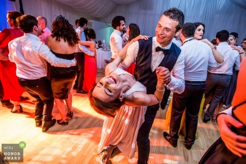 Bride and groom smiling and dipping on the dance floor at this Romania reception party