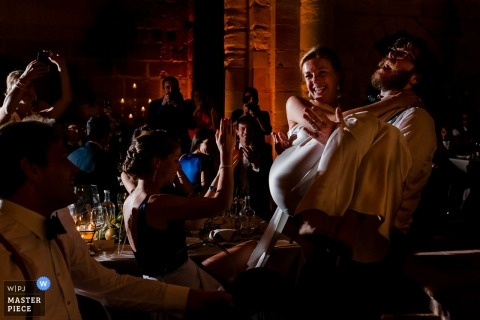 Spain Wedding Photojournalist | the bride is carried by her husband at this reception party
