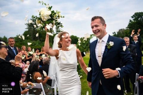La célébration commence avec des pétales de fleurs à la fin de la cérémonie de mariage en plein air d'Ipswich MA