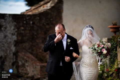 The bride is being escorted to her at wedding ceremony by her father who is wiping tears in Tuscany
