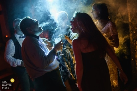 Sofia Wedding Photojournalist | smoke and blue lights fill the air at this Bulgaria wedding reception party