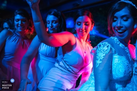 Rio de Janeiro/RJ - Brazil bride and her entourage dance under red and blue DJ lights at the reception