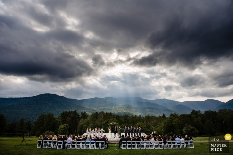 Stowe, VT Wedding Photojournalism | rays of light Stream through storm clouds overhead at this outdoor new England wedding ceremony