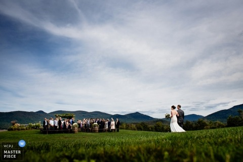 The bride and her father make the long walk through the field to the outdoor ceremony in Chittenden, Vermont