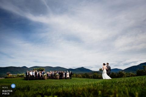 De bruid en haar vader maken de lange wandeling door het veld naar de buitenceremonie in Chittenden, Vermont