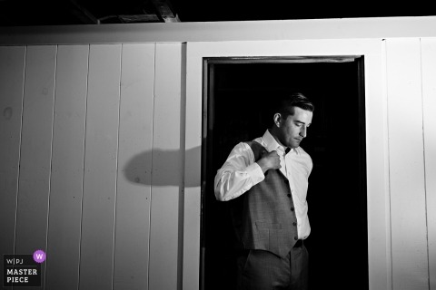 The groom gets into his suit inside one of the camp cabins   Dublin, NH