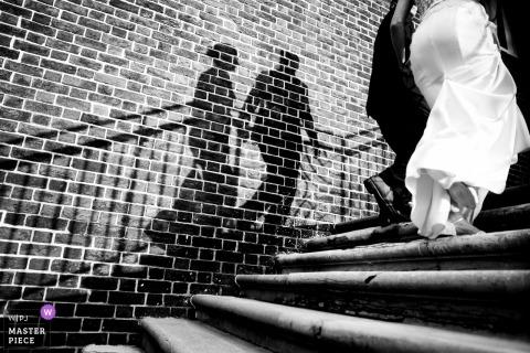 Baltimore Country Club-huwelijksfoto van de bruid en de bruidegom die stappen met hun schaduwen beklimmen op een bakstenen muur.