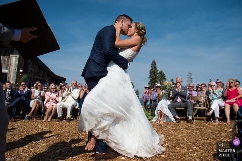 Lake Tahoe Wedding Fotojournalist | de bruid en bruidegom Wissel een gepassioneerde kus uit tijdens hun openluchtceremonie in Californië