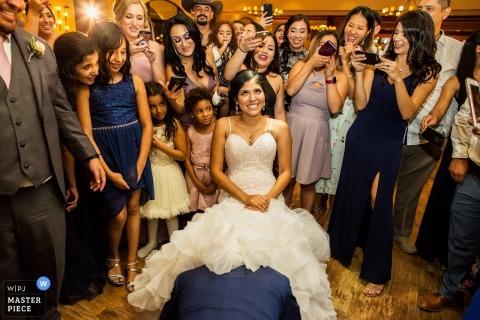 Garre Vineyard & Winery, fotografia di matrimonio Livermore della sposa sulla pista da ballo circondata dalla famiglia e dagli ospiti mentre lo sposo ritira la giarrettiera da sotto il vestito.
