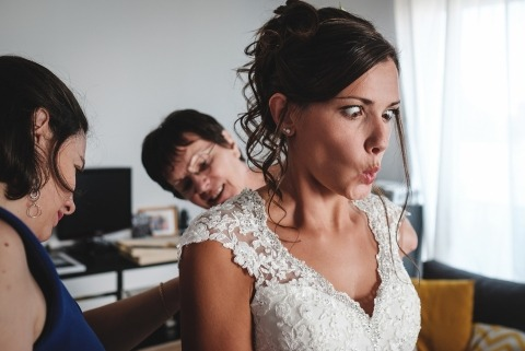 Mariage Journalisme Beauté Photos de la mariée qui croise les yeux alors qu'elle réagit à ce que sa robe soit boutonnée par derrière