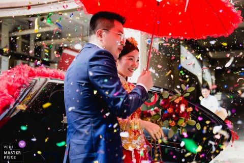 Fuzhou Wedding Photojournalist | red umbrella protects China bride and groom from confetti showers