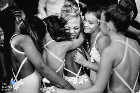 Penne d'Agenais, France wedding photograph of the bride hugging dance batton girls