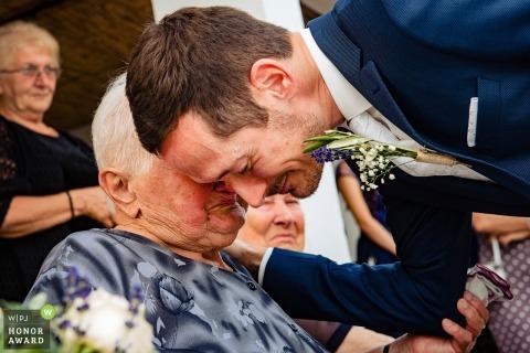 Momento emocional entre el novio de Budapest y su abuela sentada en una silla.