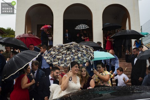 Guests and the bride in Valencia trying to avoid the rain after the ceremony