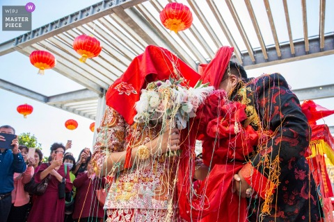 Beijing Wedding Photojournalist | under cover bride and groom in red
