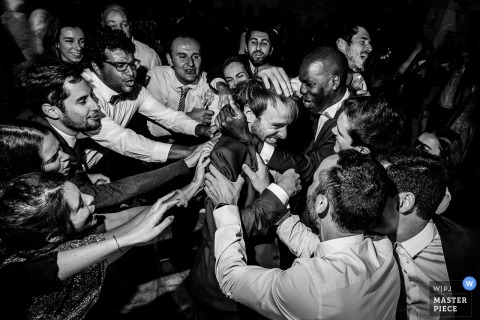 Haute-Garonne Wedding Photojournalist | the groom is surrounded by his friends at this Occitanie wedding reception