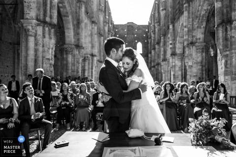 De bruid en bruidegom omarmen bij het altaar tijdens hun San Galgano-abdij, de huwelijksceremonie van Siena