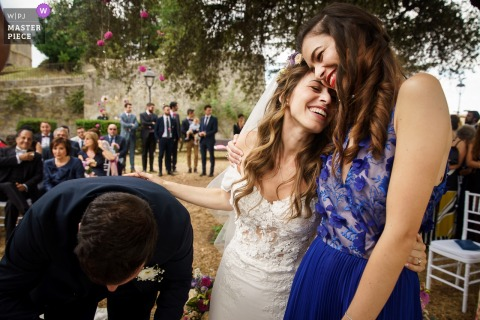 Rome Wedding Photojournalist | the bride hugs her dear friend after the Lazio wedding ceremony