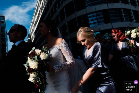 Tower Pier, London wedding photograph of bride walking with her flower boquet in the sun and shadows.
