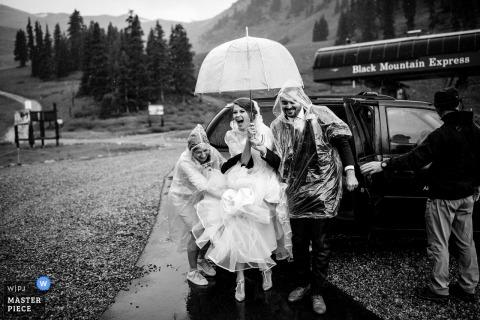 Arapahoe Basin, CO huwelijksfoto van de bruid die met paraplu in de regen op huwelijksdag loopt.