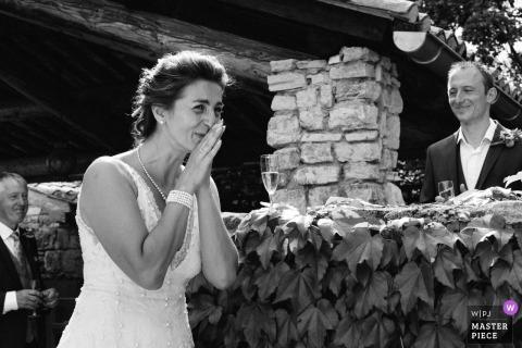Le Clos d'HulliasArdèche婚禮照片的新娘用手在她的臉上作出反應。