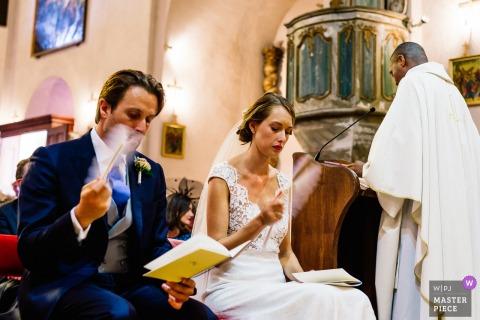 Hete huwelijksceremonie - kerkhuwelijksfoto van bruid en bruidegom met ventilators