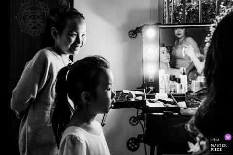 Fotojournalist Zhejiang Wedding | Jonge meisjes kijken toe terwijl de bruid haar make-up aanbrengt
