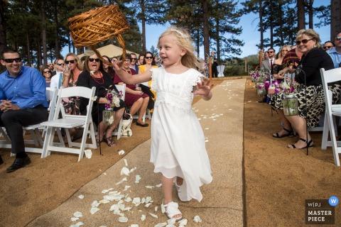 Lake Tahoe Wedding Fotojournalist | Het de bloemmeisje van Californië dumpt haar bloemblaadjesmand ondersteboven tijdens de openluchtceremonie