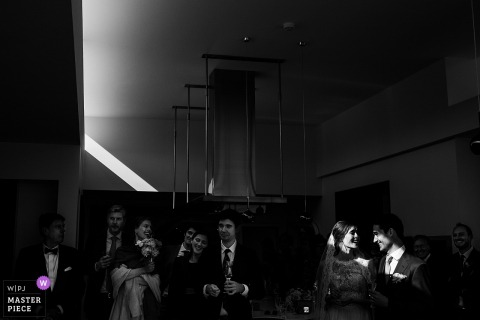 Keerbergen Wedding Photojournalist | a shaft of light illuminates the bride and groom in this black-and-white photo
