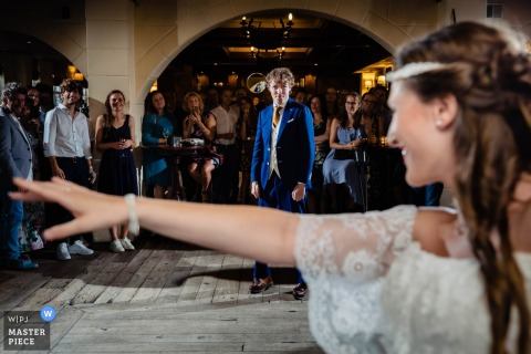 Eindhoven Wedding Photo | the bride looks over her shoulder at her husband on the dance floor