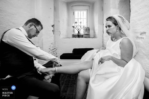 Heeswijk Dinther Wedding Fotojournalist | Zwart-wit beeld van de bruid die hulp van de bruidegom met haar schoenen ontvangt