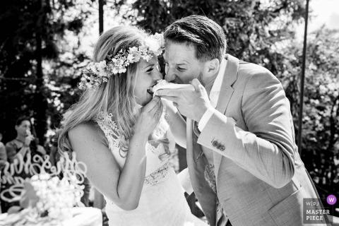 Fotojournalist van de bruiloft in Frankrijk Zwart-witte foto van de bruid en de bruidegom die cake, een beetje aan de slordige kant eten
