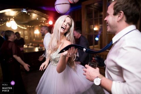 Franse huwelijksfoto in Chamonix van de bruid zacht trekkend haar bruidegomsstropdas op de dansvloer
