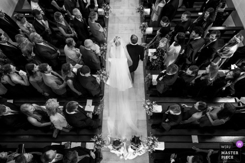 Lucht huwelijksfoto van de bruid en haar vader die onderaan de kerkdoorgang in Zwitserland lopen