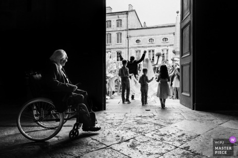 Lyon Wedding Photojournalist | a man in a wheelchair watches the bride and groom exit the church in Auvergne-Rhône-Alpes