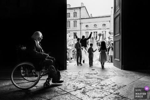 Fotojournalist van Lyon Wedding | een man in een rolstoel kijkt toe hoe de bruid en bruidegom de kerk verlaten in Auvergne-Rhône-Alpes