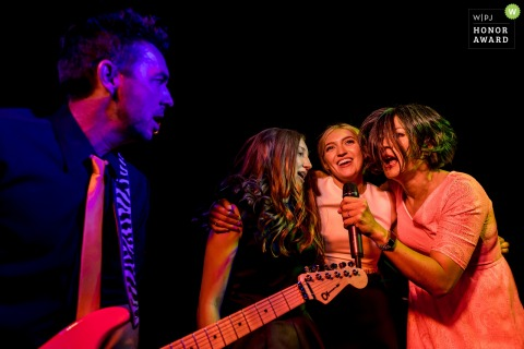 Bridesmaids singing into a microphone at the reception in Seattle with the bands guitarist