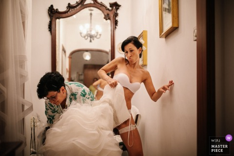 Portofino Wedding Photojournalist | Genoa bride stepping into her wedding gown with some help - Color photography