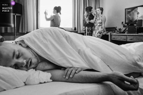 Fotojournalist van de bruiloft in Slovenië | Zwart-wit foto van Een man slaapt in een hotelbed terwijl de vrouwen zich klaarmaken