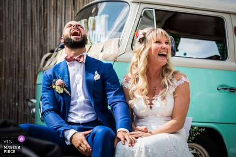 Breda (Netherlands) outdoor wedding reception laughter for this bride and groom sitting before a vintage Volkswagen bus